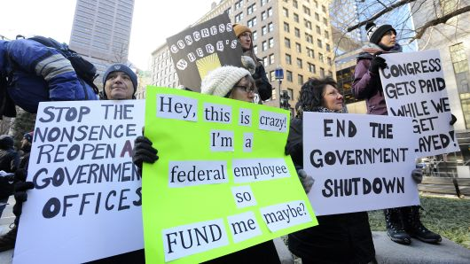 Demonstrator hold signs during a protest rally by government workers and concerned citizens against the government shutdown on Friday, January 11, 2019 at Post Office Square near the Federal building, headquarters for the EPA and IRS in Boston.