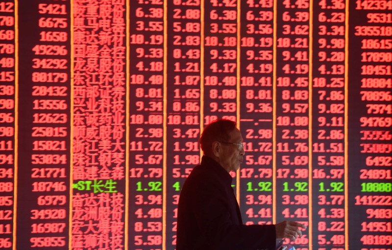 © Reuters. Man is seen in front of an electronic board showing stock information on the first day of trading in the Year of the Pig at a brokerage house in Hangzhou