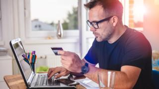 Man at laptop with payment card