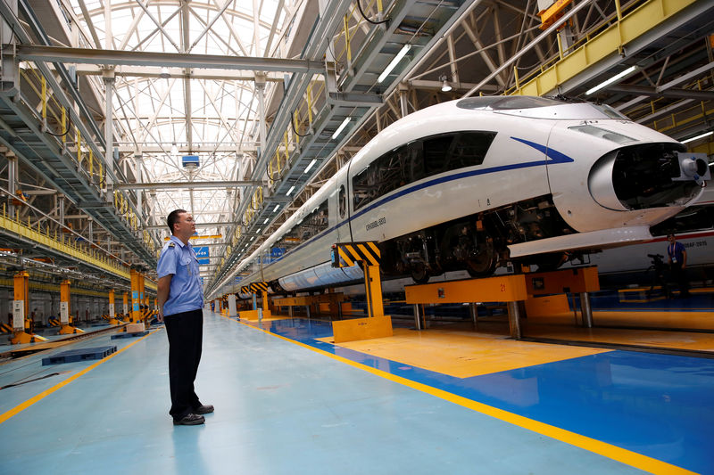 © Reuters. FILE PHOTO: A worker stands next to a high-speed train at the maintenance and repair depot of China Railway High-speed (CRH) rail service during a media tour in Beijing