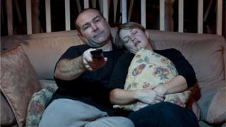 Man and woman falling asleep while watching TV on the sofa