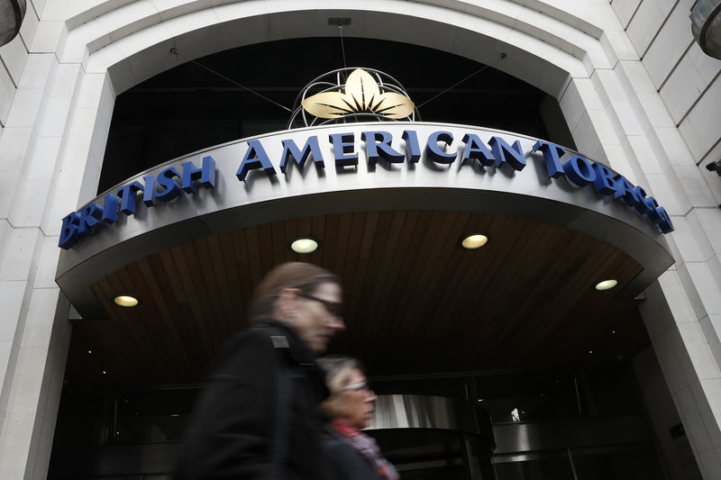 © Reuters. FILE PHOTO:  People walk past the British American Tobacco offices in London