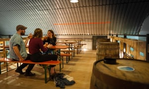 Three people drink at a communal table at The Runaway Brewery Ltd. Manchester