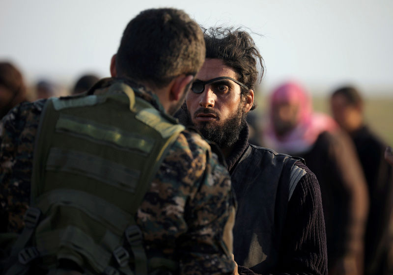 © Reuters. FILE PHOTO: A fighter from Syrian Democratic Forces (SDF) checks a man near the village of Baghouz, Deir Al Zor province