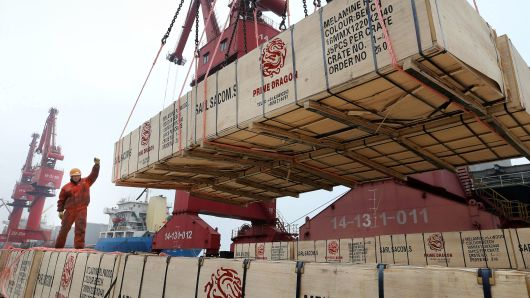 A worker gestures as a crane lifts goods for export onto a cargo vessel at a port in Lianyungang, Jiangsu province, China February 13, 2019.