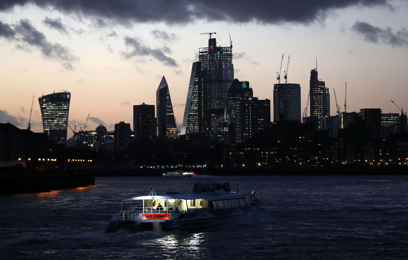 © Reuters. A river boat cruises down the River Thames as the sun sets behind the Canary Wharf financial district of London