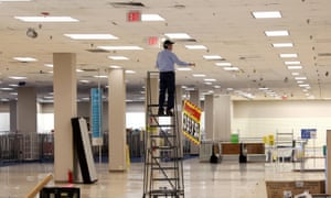 A worker removes sale banners inside a closed Sears department store in Nanuet, New York, one day after it closed as part of multiple store closures on 7 January.