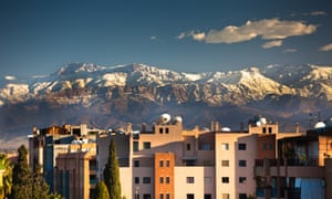 View of Marrakech buildings, with snow-capped Atlas Mountains as backdrop.
