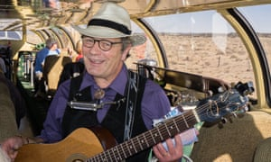 A musician strumming folk songs onboard the Williams to South Rim train.