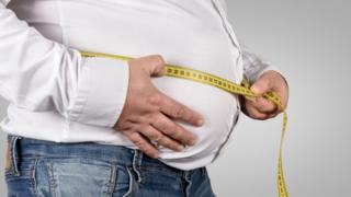 Obese man measuring belly