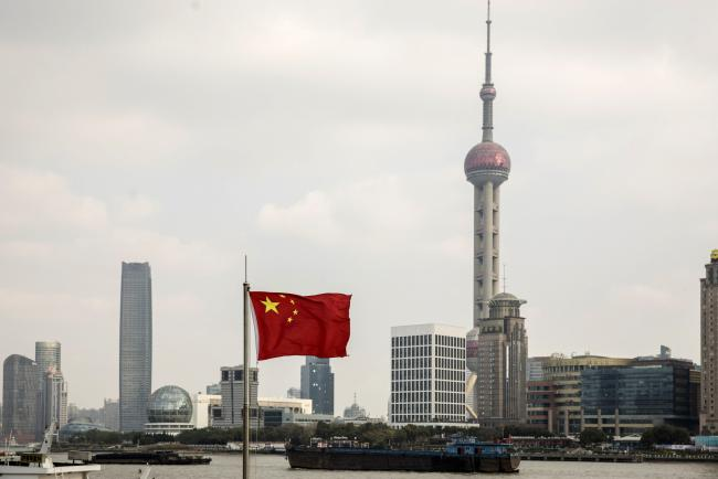 © Bloomberg. A Chinese national flag flies as skyscrapers of the Pudong Lujiazui Financial District stand across the Huangpu River in Shanghai, China, on Friday, Dec. 28, 2018. China announced plans to rein in the expansion of lending by the nation's regional banks to areas beyond their home bases, the latest step policy makers have taken to defend against financial risk in the world's second-biggest economy. Photographer: Qilai Shen/Bloomberg