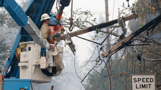 PG&E crews remove power lines damaged by fire off Bille Road in Paradise, Calif., on Saturday, Nov. 10, 2018.