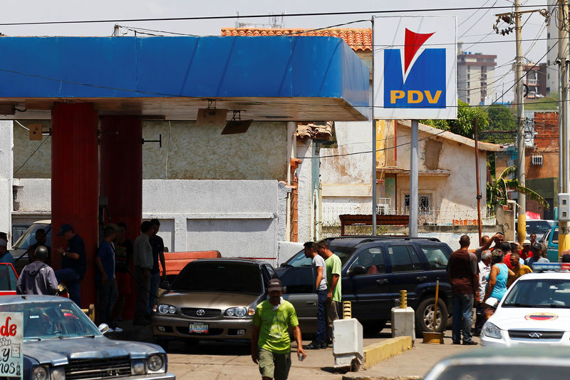 © Reuters. People with vehicles wait in line to attempt to refuel at a gas station of the state oil company PDVSA in Maracaibo