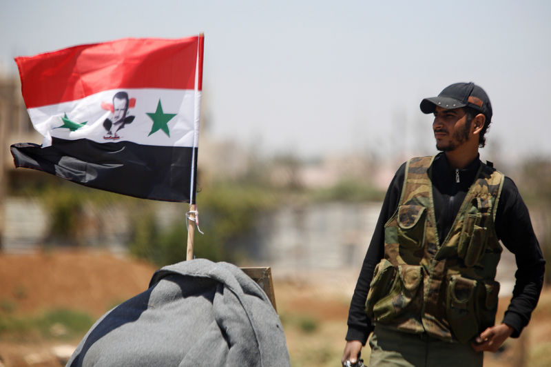 © Reuters. FILE PHOTO: A Syrian army soldier stands next to a Syrian flag in Umm al-Mayazen, in the countryside of Deraa