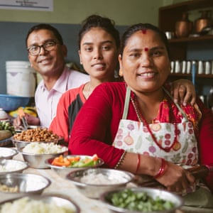 Three Indian people in a kitchen with bowls of ingredients for dishes they are preparing.