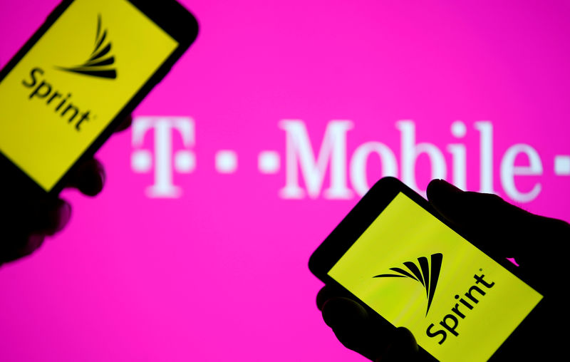 © Reuters. FILE PHOTO: A smartphones with Sprint logo are seen in front of a screen projection of T-mobile logo, in this picture illustration