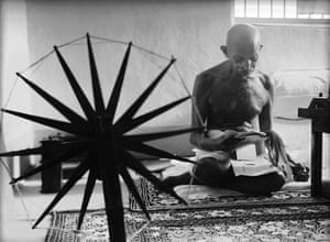 Gandhi reading near a spinning wheel at home in 1946