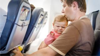 Unhappy baby on plane with dad