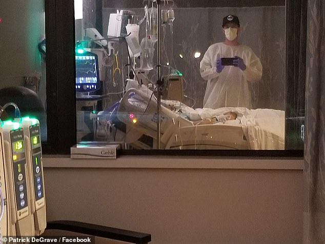 The patient, of Burlington, Wisconsin, was hospitalized this week, coughing and struggling to breathe, his brother, Patrick DeGrave (pictured next to his brother's bed), said