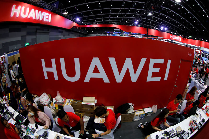 © Reuters. FILE PHOTO: Workers sit at the Huawei stand at the Mobile Expo in Bangkok