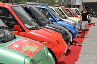 An Indian woman walks past a line of electric Reva motorcars prior to a Reva car rally held to celebrate World Environment Day in New Delhi on June 5, 2009.