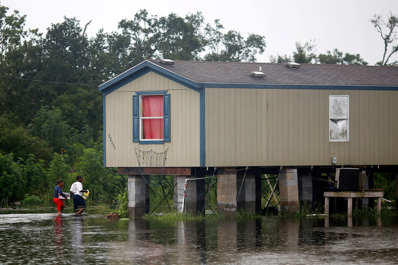 © Reuters. Residents walk through flood water back to their raised house during Hurricane Barry in Plaquemines Parish