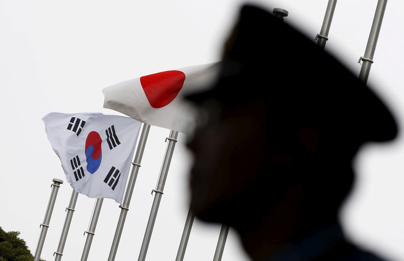 © Reuters. FILE PHOTO: Police officer stands guard near Japan and South Korea national flags at a hotel in Tokyo