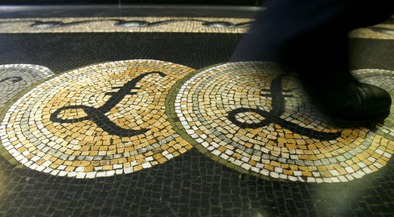 © Reuters. File photograph shows an employee walking over a mosaic depicting pound sterling symbols on the floor of the front hall of the Bank of England in London