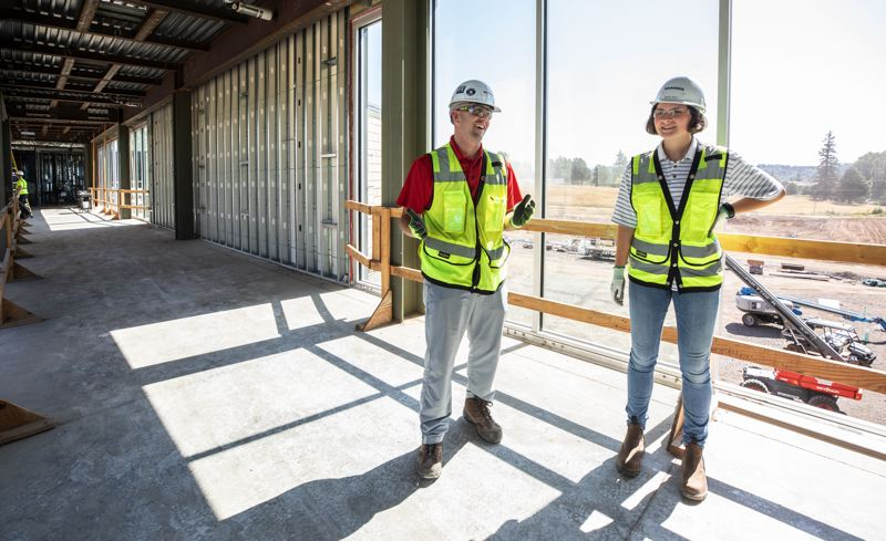 TRIBUNE PHOTO: JONATHAN HOUSE - Grace Gary, right, and Sean Walker stand in the skybridge of the new Sherwood High School, which is slated for completion in May 2020.