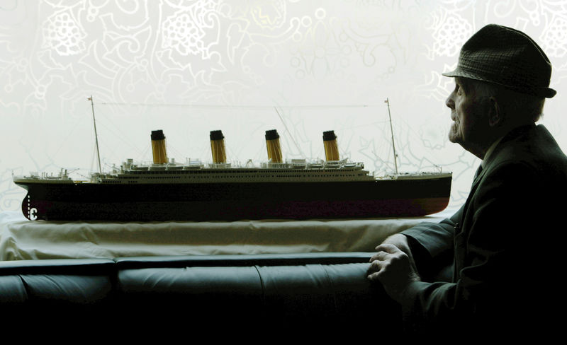 © Reuters. FILE PHOTO: JOHN PARKINSON PRESIDENT OF THE BELFAST TITANIC SOCIETY SITS NEAR A MODEL OF THE TITANIC IN BELFAST.