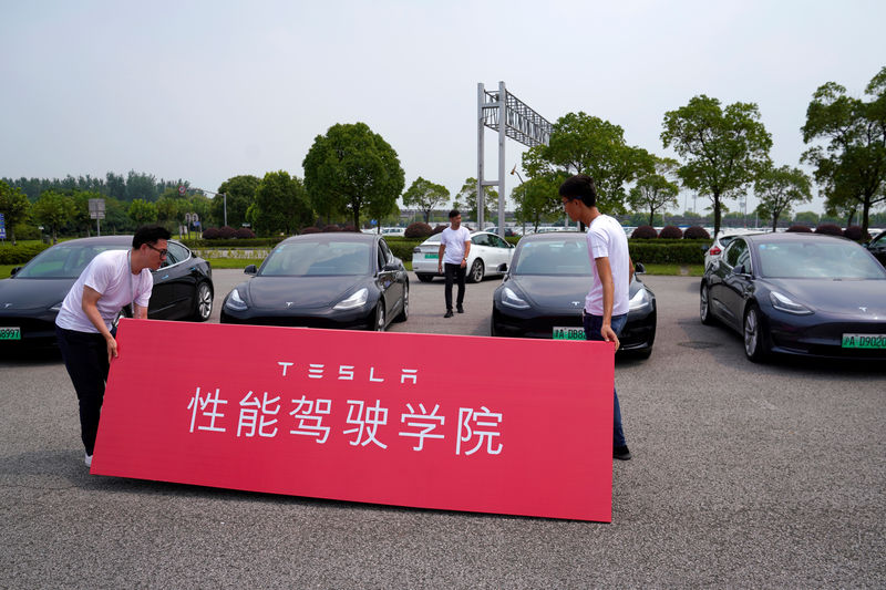 © Reuters. People attend a Tesla performance driving school promotional event at Shanghai International Circuit