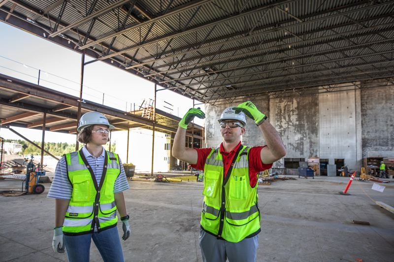 TRIBUNE PHOTO: JONATHAN HOUSE - Grace Gary, left, and Sean Walker talk about the building materials in the cafeteria of the new Sherwood High.