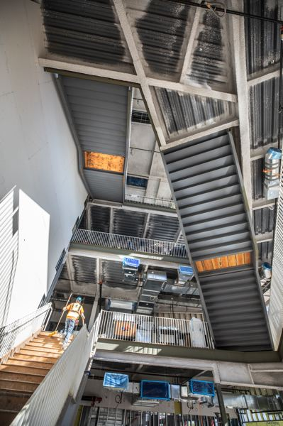 TRIBUNE PHOTO: JONATHAN HOUSE - A construction worker climbs up the Cascade Point staircase in the new Sherwood High School.