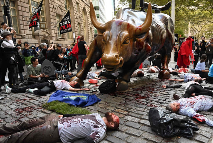 Protesters covered in fake blood gather around the Wall Street bull during an Extinction Rebellion demonstration in New York