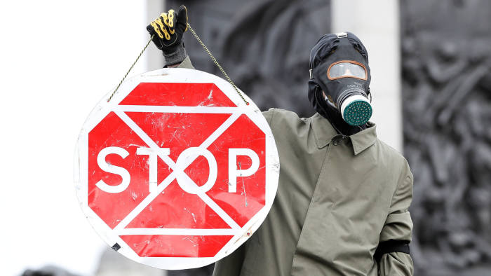 A protester holds a stop traffic sign overlaid with the Extinction Rebellion symbol. The protest is designed to increase awareness of climate change.