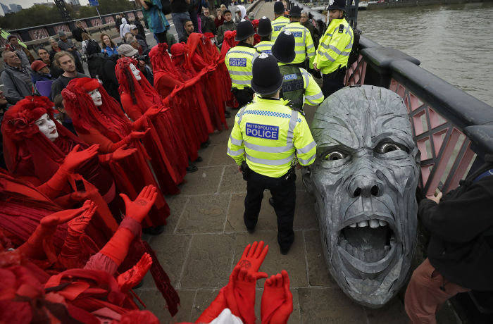 Protestors gather around the head of a statue confiscated by police on Lambeth bridge on Monday