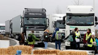 Activists formed a human chain, lay on hay bales and dumped old fridges and microwaves outside Amazon depot