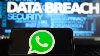 In this photo illustration, the Whatsapp logos is seen on a Huawei smartphone with the word Data breach on a laptop monitor.