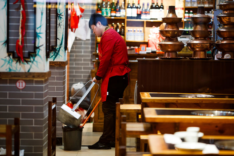 © Reuters. A waiter cleans the floor of a restaurant after closing hours in Beijing