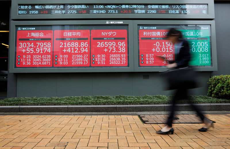 © Reuters. A woman walks past an electric screen showing world markets indices outside a brokerage in Tokyo