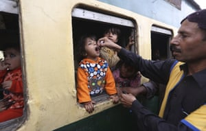 A health worker gives a polio vaccination to a child in a Karachi railway station in Pakistan, 18 November 2019.