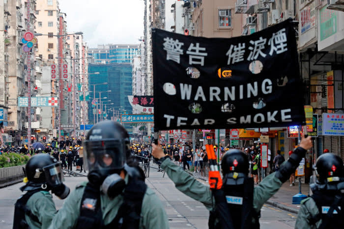 A riot police raises a warning flag as they try to disperse anti-extradition bill protesters by tear gas at Sham Shui Po in Hong Kong, China August 11, 2019. REUTERS/Tyrone Siu - RC1940424350