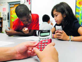 Fourth-graders Nathaniel Baldwin (left), Jonathan Halleen (center) and Micah Blanton from Garland's Watson Technology Center have a firm grasp on how using the clickers can enhance a classroom lesson.