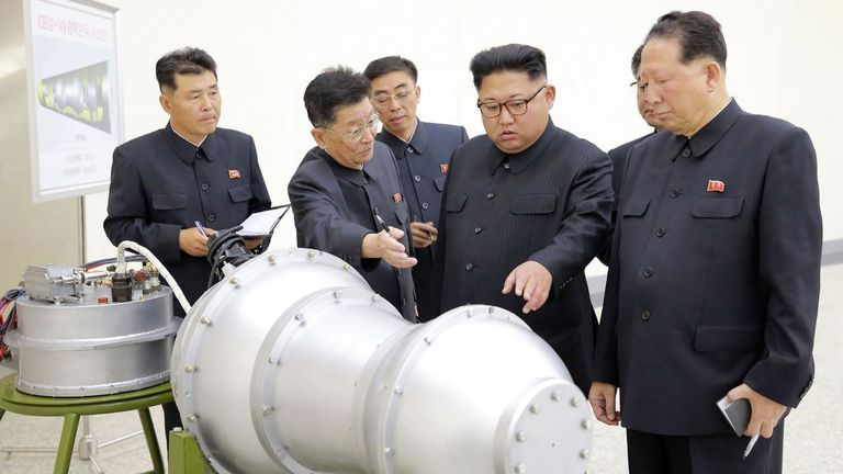 TOPSHOT - This undated picture released by North Korea's official Korean Central News Agency (KCNA) on September 3, 2017 shows North Korean leader Kim Jong-Un (C) looking at a metal casing with two bulges at an undisclosed location. North Korea has developed a hydrogen bomb which can be loaded into the country's new intercontinental ballistic missile, the official Korean Central News Agency claimed on September 3. Questions remain over whether nuclear-armed Pyongyang has successfully miniaturise