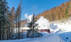 White snow and blue skies: a historical steam train running full speed to Brocken mountain in the Harz region.