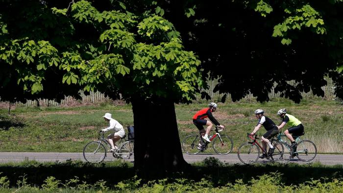 Cyclists ride their bicycles in the sunshine in Richmond Park in south west London on May 7, 2018. - Temperatures on Monday were predicted to reach 29C (84.2F) in parts of the south east of England, as people enjoyed the sunny weather over the three-day bank holiday weekend. (Photo by Adrian DENNIS / AFP) (Photo credit should read ADRIAN DENNIS/AFP via Getty Images)