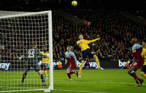 An unmarked Mesut Ozil heads over.