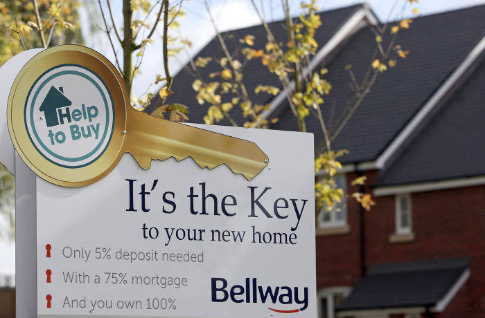"""An advertisement for the U.K. Government's new """"Help to Buy"""" scheme sits outside a row of new residential homes at a Bellway Plc real estate site in Northampton, U.K., on Thursday, Oct 10, 2013."""