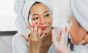 Woman looking at herself in the mirror, applying cream on her face