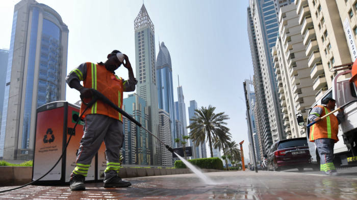 Foreign workers clean Dubai's Sheikh Zayed road on October 2, 2019 in Dubai. - With the highest tower in the world, grand commercial centres and artificial islands, Dubai projects an image of prosperity, even as the city-state races to court investors to bolster a flagging economy. Despite boasting the most diverse economy in the Gulf region, the emirate's vital property, tourism and trade sectors have weakened in recent years. (Photo by KARIM SAHIB / AFP) (Photo by KARIM SAHIB/AFP via Getty Images)